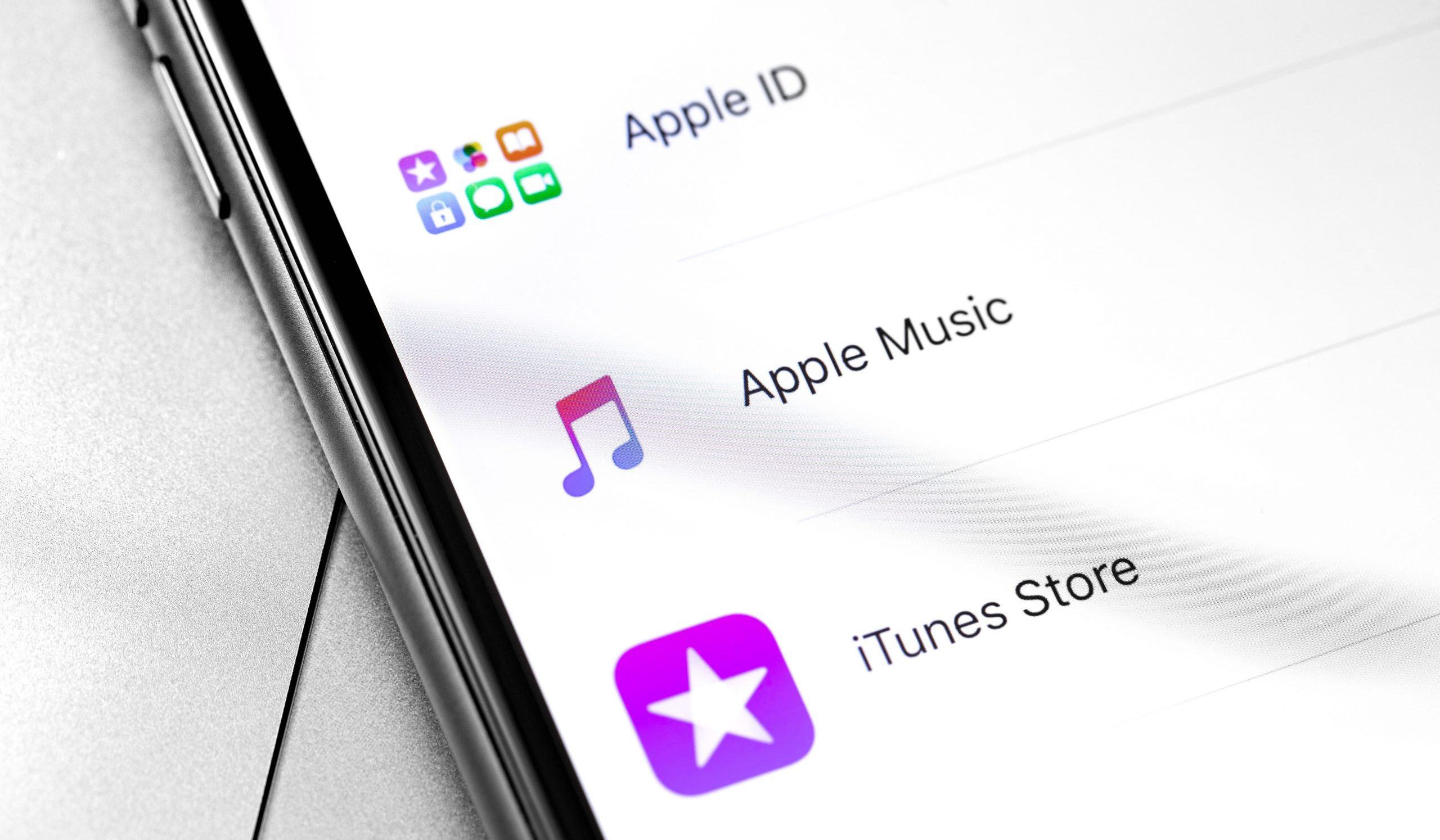 Tela de iPhone com opções de Apple ID, Apple Music e iTunes Store.